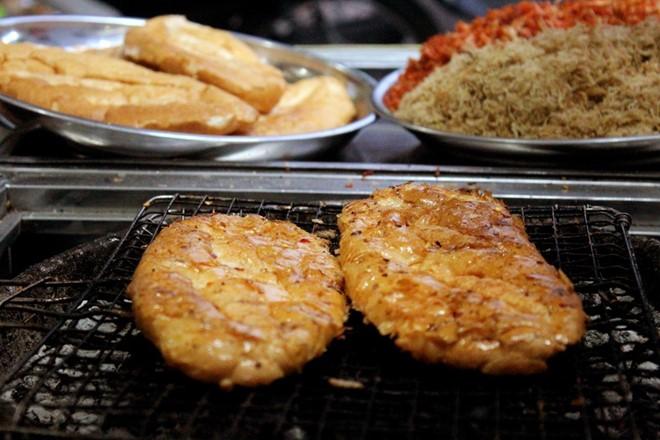 Bánh mì nướng muối ớt là món ăn đơn giản có nguồn gốc từ Châu Đốc, An Giang. Bánh mì được đập dẹp, nướng trên bếp than, phết lớp bơ mỏng, nước sốt sate lên bánh. Ảnh: Huỳnh Duyên.
