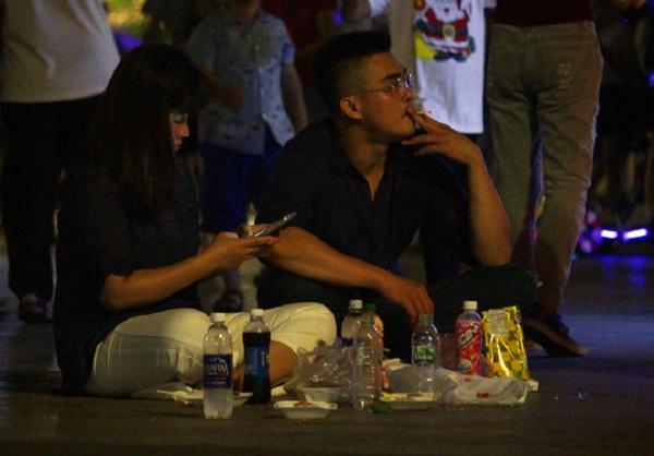 Sau khi vui chơi, nhóm bạn trẻ ngồi ngay giữa phố đi bộ, bày biện đồ ăn thức uống nhếch nhác khắp nơi.