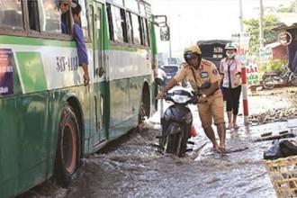CSGT dắt xe cho người dân trên đoạn đường ngập nước. Ảnh: Trường Sơn