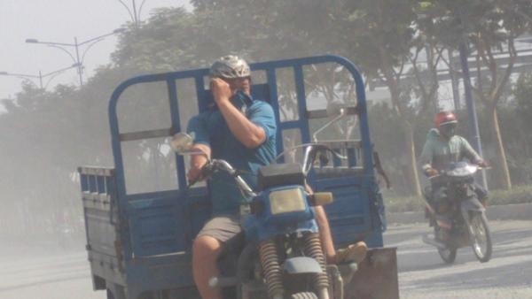 """Người đi đường lấy tay che kín mặt, mũi vì """"bão bụi"""" trên đường Trần Văn Giàu, cửa ngõ phía Tây TPHCM"""