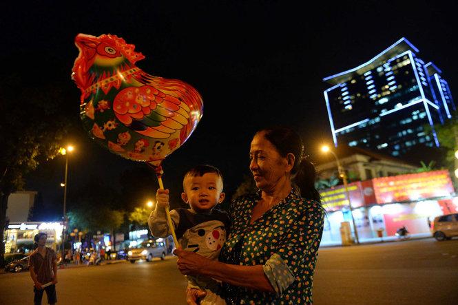 Hai bà cháu cùng với quả bong bóng hình con gà tương trưng cho năm Đinh Dậu 2017 dạo chơi khu trung tâm - Ảnh: HỮU KHOA