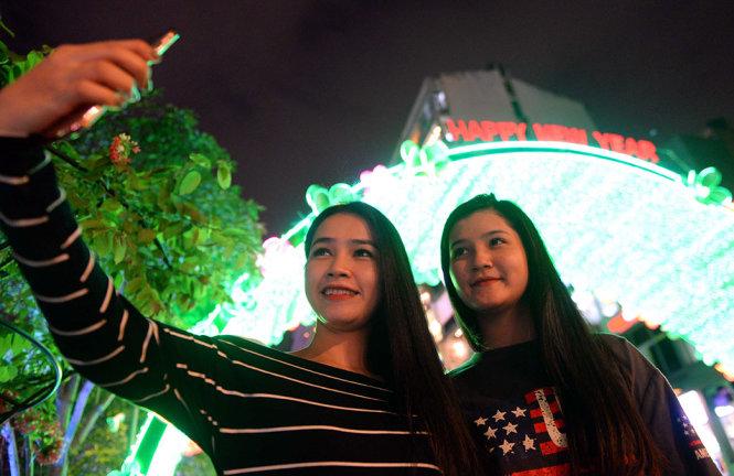 Hai bạn trẻ selfie trước dòng chữ Happy New Year trên phố đi bộ Nguyễn Huệ - Ảnh: HỮU KHOA