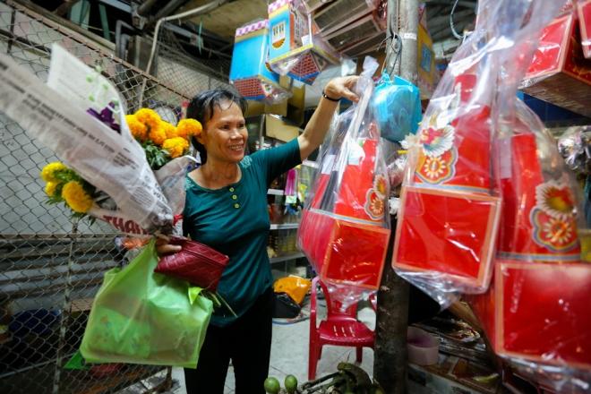 Cô Lê Quỳnh Vui (53 tuổi, đường Bạch Đằng, quận Tân Bình) mua hoa, cá và bộ đồ vàng mã cúng Táo quân.