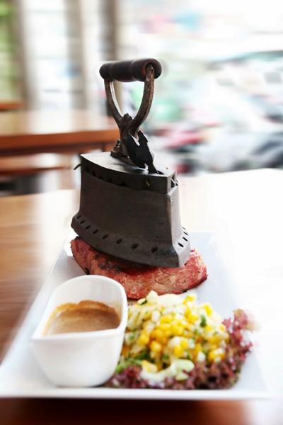 Độ chín của thịt bò phụ thuộc thời gian thực khách đặt chiếc bàn ủi - bên trong có chứa than với nhiệt độ cao, lên trên miếng thịt bò trong bao lâu. Món ăn được dùng kèm với salad trái cây có tác dụng kích thích vị giác làm từ xoài, lê và rau xà lách. Ảnh: Facebook quán.