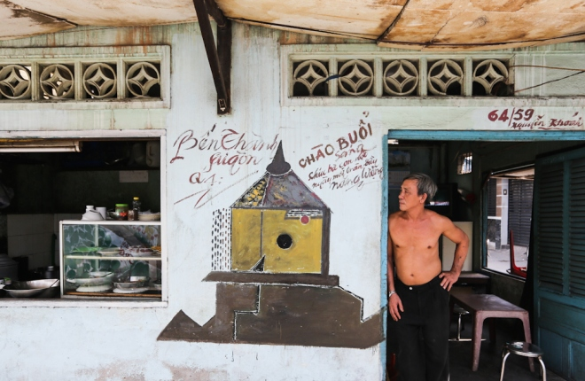 """Hình ảnh chợ Bến Thành được vẽ trước quán của ông Cao Vĩnh Cơ. """"Bức họa này được vẽ 8 tháng rồi. Trước kia nhìn quán cũ kỹ lắm, có mấy bức tranh nhìn sinh động hơn và có nhiều khách đến ăn nữa"""", ông Cơ nói."""