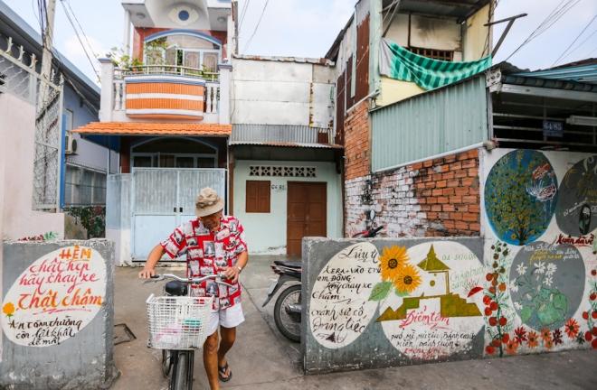 """Vào thời điểm cuối năm, ông Minh thường xuyên dắt xe đạp đi vẽ, """"khoác áo mới"""" cho các con hẻm trong dịp Tết. """"Không chỉ người dân, lãnh đạo phường mà con cái tôi cũng thích nghệ thuật nên ủng hộ việc làm ý nghĩa này. Tôi không ép mình ngày nào cũng phải vẽ, khi nào mình có đề tài, cảm hứng thì vẽ thôi nhưng gần Tết thì vẽ nhiều hơn"""", ông Minh chia sẻ."""