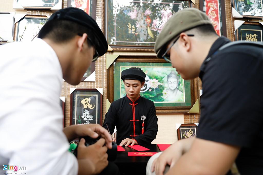 Hai thanh niên ngắm nhìn ông đồ trẻ Đức Dự thi triển thư pháp.