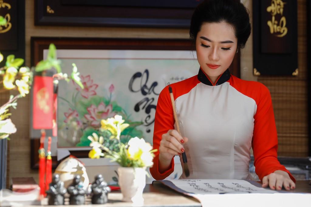 Cô gái Nguyễn Mỹ Kim ngồi vào gian hàng tập viết với bút lông. Kim cho biết khi nghe tin phố ông Đồ hoạt động sau khi làm spa tranh thủ đến vui chơi, chụp ảnh cùng bạn bè.