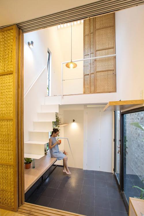 Điểm mấu chốt giúp căn hộ có vẻ rộng rãi hơn là hệ cửa lùa tre giúp không gian riêng tư và sinh hoạt chung được đóng mở linh hoạt. Nhờ gạch lỗ và lớp cây xanh, chủ nhà có thể mở cửa kính khung lớn ra nhận ánh sáng, khí trời.