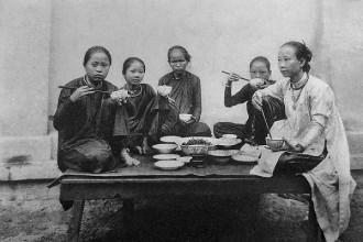 Trong ảnh là bức thể hiện bữa cơm gia đình của phụ nữ trung lưu thành thị 1901. Y phục của phụ nữ không có sự cách biệt, đều là áo dài sẫm đen, may rộng, suông đuột không eo, cổ trệt hoặc đứng