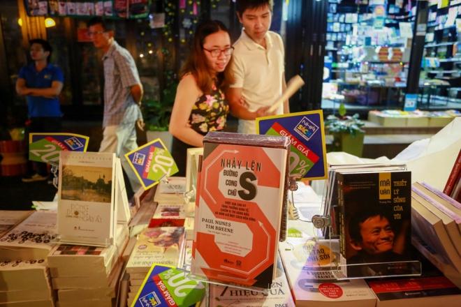 """Những người yêu sách chăm chú đọc và chọn mua ấn phẩm tại một gian hàng. Các tác phẩm văn học, chân dung nhân vật, sách kinh tế... luôn thu hút mọi người. Ngoài hoạt động trưng bày và bán sách, ở không gian này còn diễn ra nhiều buổi giao lưu như tọa đàm chủ đề """"Doanh nhân khởi nghiệp - chia sẻ bài học thành công"""", sẽ diễn ra từ 18h ngày 26/1 (tức ngày 29 Tết)."""