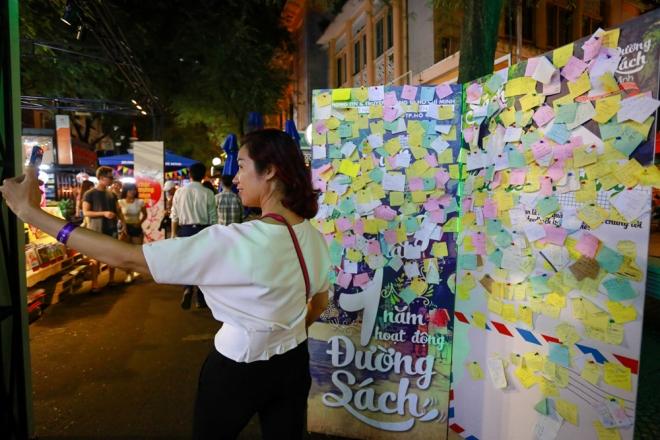 Một du khách selfie bên tấm bảng ghi lại cảm xúc  của nhiều người khi tham quan Đường sách. Trong những ngày diễn ra, ở đây còn có các hoạt động như biểu diễn nhạc cổ truyền, trình diễn guitar, giao lưu với các nhà văn trẻ...