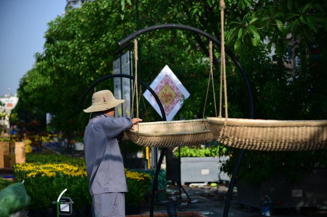Công nhân đang lắp đặt những lẵng đựng hoa bằng tre đan - Ảnh: HỮU THUẬN