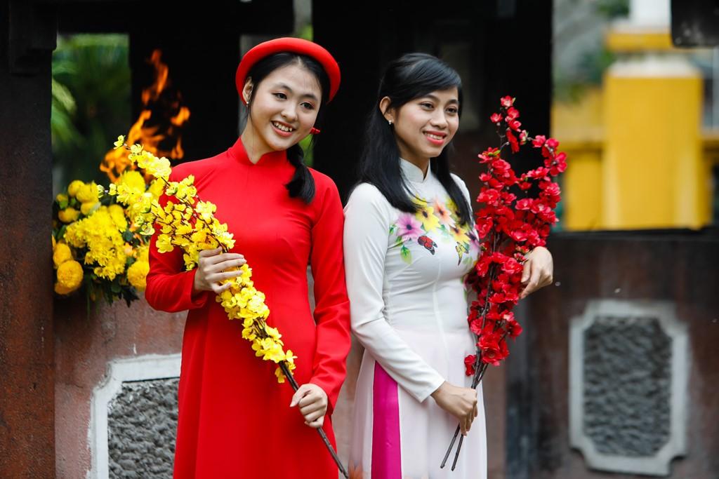 Phần lớn khách đến lăng mặc áo dài, mang theo đạo cụ là những cành hoa để tạo dáng.