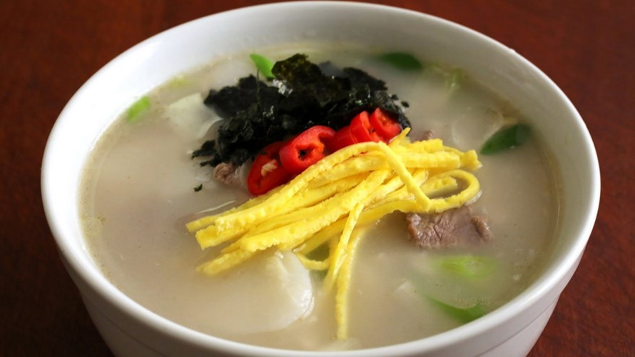 """Các món ăn ngày Tết của Triều Tiên rất phong phú với hơn 20 món, trong đó không thể thiếu món ttok-kuk - món ăn được làm từ nước cơm, với bánh gạo và đậu xanh. Ttok-kuk có ý nghĩa là """"tăng xuân"""", người Triều Tiên tin rằng vào ngày đầu tiên của năm mới nếu dùng một bát Ttok-kuk thì họ sẽ được thêm một tuổi nữa bởi họ quan niệm khi họ thêm một tuổi là khi hết năm cũ chứ không phải sau ngày sinh nhật như những nơi khác."""