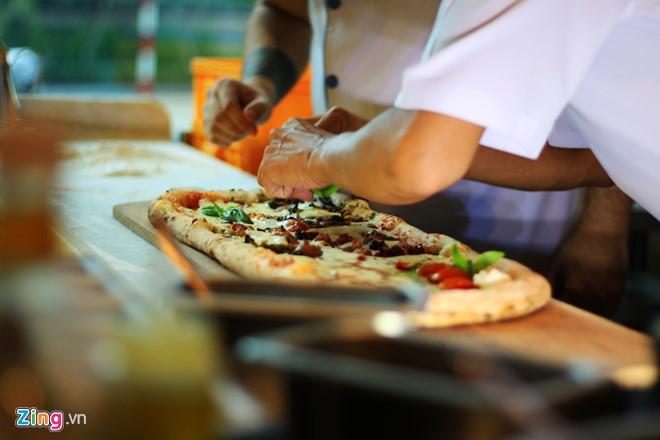 Bánh có thời gian nướng là 90 giây kể cả lần nghỉ thêm nhân. Nhờ kỹ thuật nướng nhanh, một số nguyên liệu như cà chua, rau thơm vẫn giữ nguyên màu sắc tươi ngon. Ảnh: An Huỳnh.