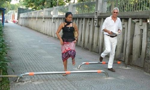 Du khách nước ngoài phải quan sát khi bước qua barie để tránh bị vấp té.