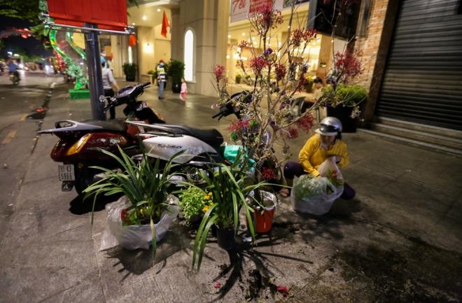 """Gần 1h, nhiều người dân vẫn kiên nhẫn chờ xin hoa từ các công nhân dọn dẹp. """"Tôi xin vài cây lan về để làm giống. Chúng tôi xin chứ không có nhào vô cướp"""", chị My chia sẻ."""