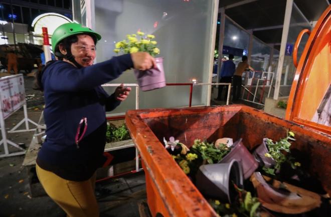 """Khi thấy hoa vứt thùng rác, bị nghiền nát, một số người dân tiếc, chạy lại lấy nhưng hầu hết bị bảo vệ ngăn lại. """"Tôi thấy hoa còn tươi mà bỏ đi như vậy phí quá nên xin lại, phải nài nỉ mãi họ mới cho"""", cô Trần Giai Cẩm (quận 6) giải thích"""