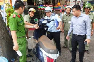 Lực lượng chức năng tạm giữ một xe máy không người nhận đậu trên vỉa hè đường Phạm Ngũ Lão - Ảnh: Lê Phan