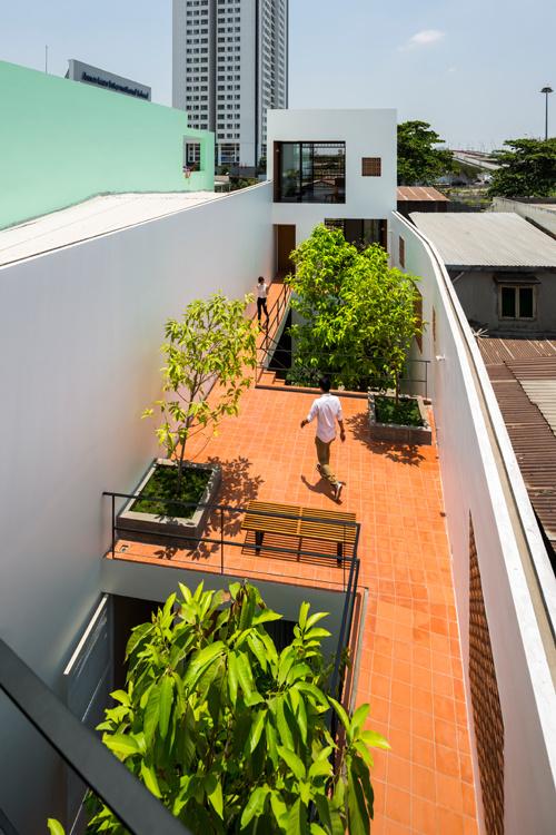 Một trong những phòng ngủ của chủ nhà nằm giữa tầng một. Phần mái được biến thành sân vườn lớn và kết nối giữa hai khối nhà. Khoảng sân vườn chung này sẽ tạo nên nhiều hoạt động thú vị cho những người sống ở đây.