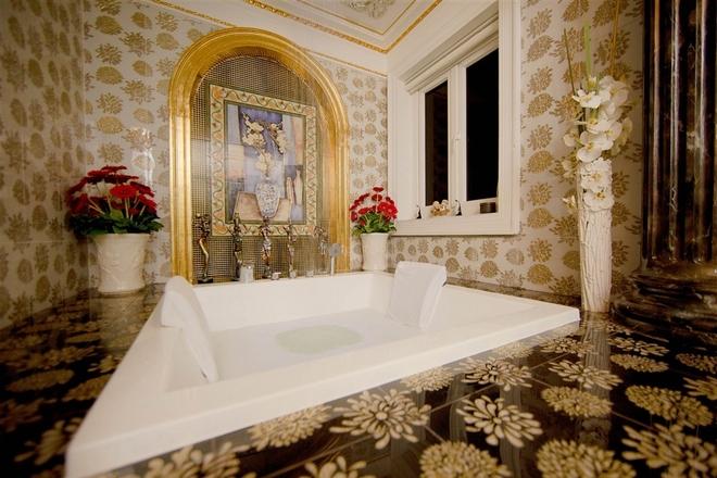 Một mảng tường trong phòng tắm được viền bằng vàng và trang trí các loại hoa tươi. Người đẹp mong muốn mỗi góc nhà là một bức tranh nghệ thuật.
