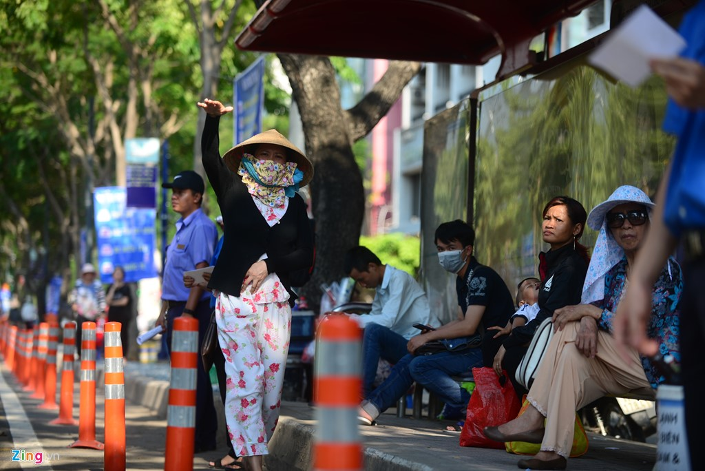 """Dải phân cách để người dân đón xe buýt được an toàn trên đường Hàm Nghi. Chị Linh, khách đón xe buýt từ quận 4 về chợ Bến Thành để bắt xe về Thủ Đức, cho biết chị rất bỡ ngỡ khi thấy trạm xe buýt dời đi và phải loay hoay một hồi mới biết trạm dời về đường Hàm Nghi. """"Trạm dài quá cũng không biết nên đón ở đâu. May nhờ có người chỉ mới biết"""", chị Linh ẵm con chia sẻ."""