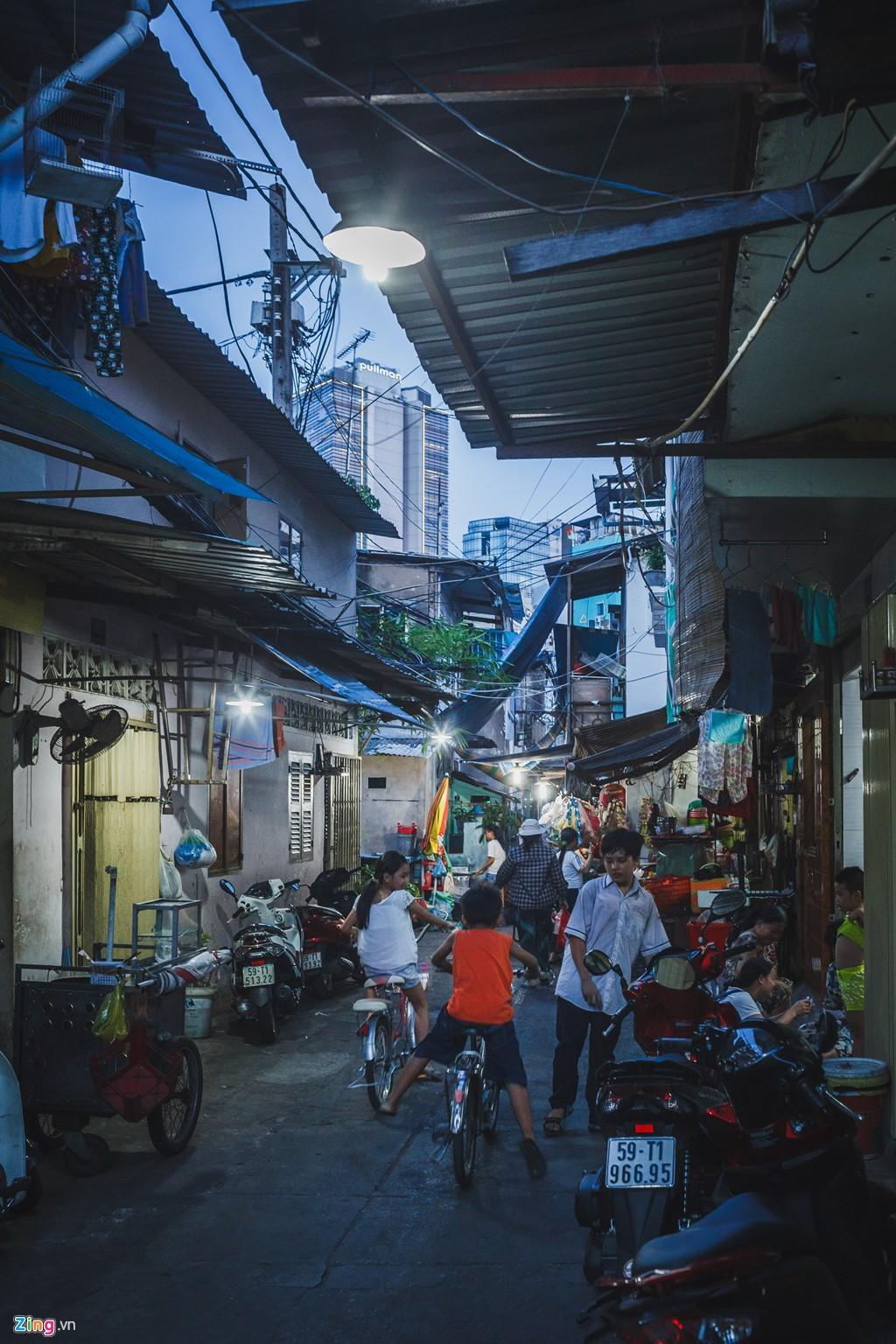 Khi trời nhá nhem tối, những toà nhà cao tầng xung quanh bắt đầu bật đèn sáng choang, hắt ánh sáng của sự phồn hoa xuống khu phố nghèo và tối tăm.