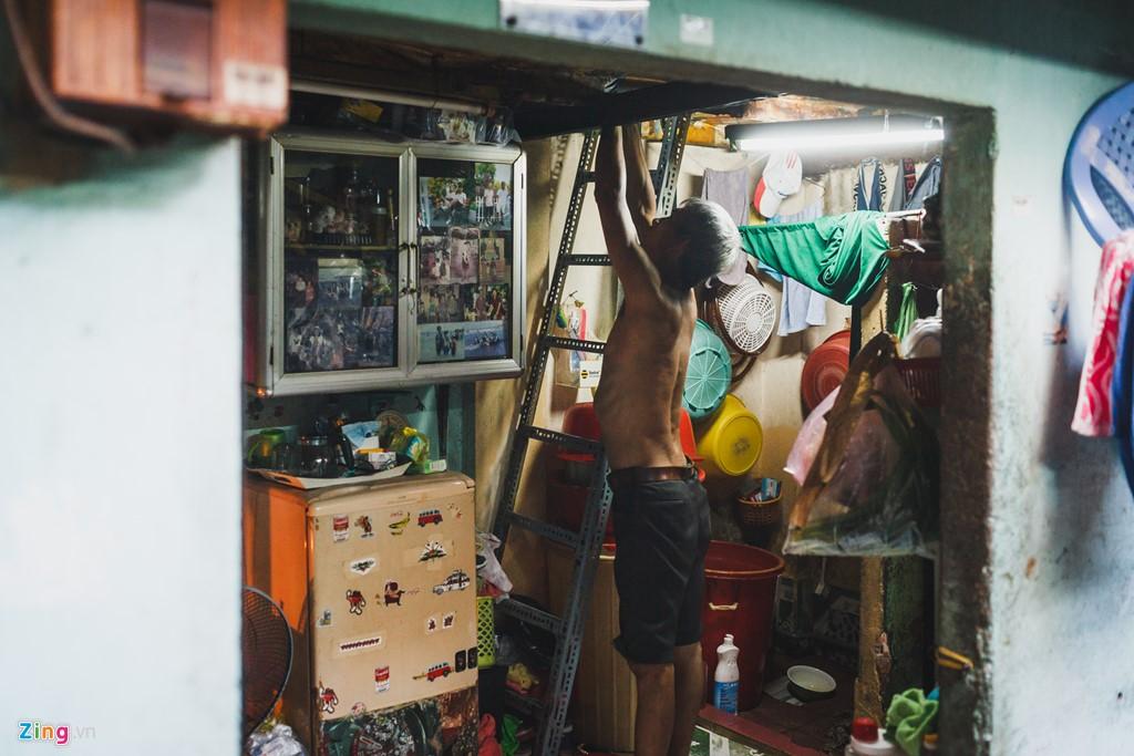 """Gia đình ông Chung Văn Sơn sinh sống tại đây từ năm 1991. Nơi gọi là """"nhà"""" của ông bao gồm một gian trệt khoảng 3 m2 để tắm giặt, rửa chén, sinh hoạt, tiếp khách,... và gian gác phía trên để ngủ."""