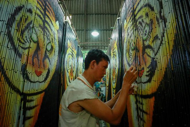 Ông Nguyễn Vũ Tạo tỉ mẩn sơn vẽ họa tiết con hổ trên tấm mành trúc. Theo ông Tạo, để làm ra một sản phẩm hoàn chỉnh phải trải qua nhiều công đoạn như lựa chọn trúc, xỏ dây, lên khung, sơn cảnh, phơi sấy sản phẩm.