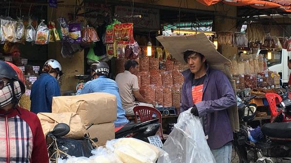 Anh Út , bốc xếp chợ Bình Tây, quận 6, TP.HCM chống chọi với nắng nóng bằng sáng kiến lấy thùng mì gói làm nón đội kéo dài đến lưng - Ảnh: Tự Trung