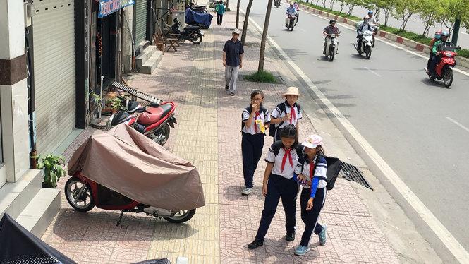 Học sinh nối dài tay áo che nắng nóng - Ảnh: Tự Trung