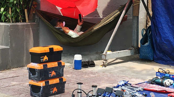 Anh thanh niên trốn vào một góc tường để trốn nắng - Ảnh: Tự Trung
