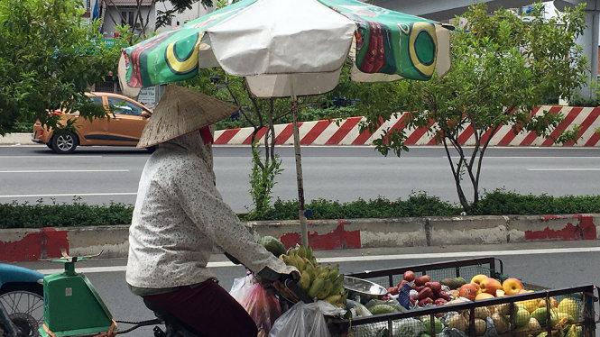 Chị bán hàng rong trùm kín trên đường Phạm văn Đồng, quận Gò vấp - Ảnh: Tự Trung