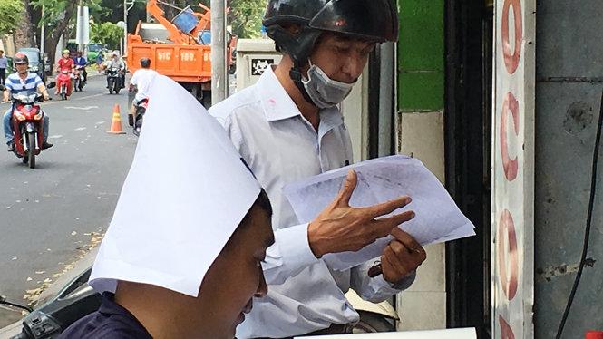 Anh thợ photocopy trên đường Nguyễn Thị Minh Khai, quận 1, TP.HCM lấy giấy sẵn có làm nón che nắng - Ảnh: Tự Trung