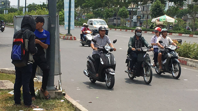 Hai thanh niên phát tờ rơi vòng xoay Nguyễn Thái Sơn, quận Gò Vấp tranh thủ núp sau tâm bảng hiếm hoi trên đường để tránh nắng - Ảnh: Tự Trung