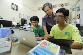Ông Đặng Quốc Anh hướng dẫn hai con là Đặng Nhật Anh (bìa phải) và Đặng Thái Anh học tại nhà - Ảnh: NHƯ HÙNG