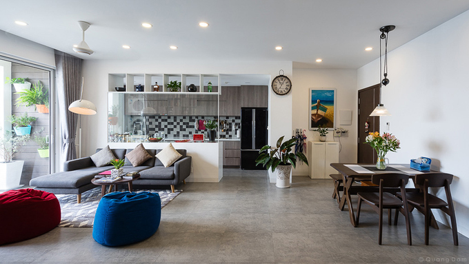 Sảnh chính, phòng khách, bàn ăn và bếp được bố trí liên hoàn. Màu sắc không gian này nhã nhặn với các tông trắng, xám và nâu trầm bên cạnh một vài vật dụng có màu tươi tắn phù hợp với hai con nhỏ.