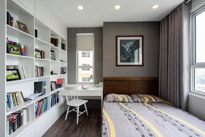 Phòng ngủ của bố mẹ có diện tích không lớn nhưng được sắp xếp tiện dụng. Màu sắc và vật liệu hài hòa, làm nền cho những quyển sách nhiều màu sắc.