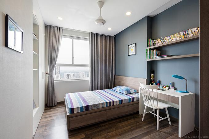 Phòng ngủ con trai có tầm nhìn thoáng ra cảnh quan sông nước bên ngoài, được bố trí ngăn nắp với hệ tủ âm tường, giường ngủ có hộc kéo và bàn học kết hợp kệ treo tường.