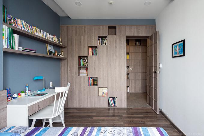 Phòng ngủ này được ngăn chia với hành lang bằng hệ tường sách đa năng là điểm nhấn về màu sắc và chất liệu.