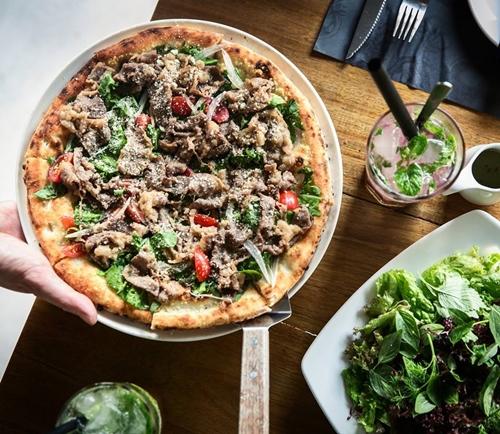 """Pizza phải đặt trước 2 ngày Quán pizza kiểu Nhật luôn đông kín khách, để có được bàn vào cuối tuần bạn phải đặt trước 2 ngày. Bánh được nướng trong lò gạch với củi từng chiếc một để đảm bảo nhiệt độ chuẩn cho bánh chín đều. Các món ăn được """"Nhật hóa"""" tạo sự đặc biệt với thực khách không ăn quen đồ Tây. Một số món pizza nổi bật là Margherita (sốt cà chua, phomai và thịt nguội), Teriyaki Chicken (thịt gà, mayonnaise, rong biển), Salmon Miso Cream (cá hồi, mozzarella, miso), Salmon Sashimi (cá hồi, hành tây, phomai)... Điều đặc biệt ở đây là bạn có thể gọi một chiếc bánh với hai nửa nhân khác nhau. Thực khách cũng có thể chứng kiến toàn bộ quá trình làm pizza trong quầy bếp. Giá một chiếc pizza ở đây từ 250.000 đến 500.000 tùy loại."""