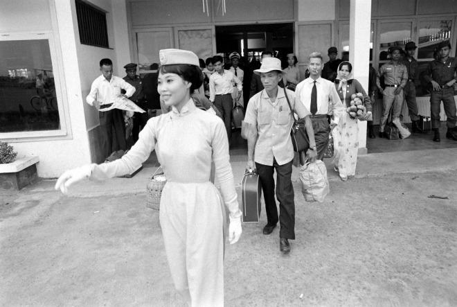 Nữ tiếp viên hàng không trong trang phục áo dài, mũ lệch và găng tay trắng đang trực tiếp dẫn khách lên máy bay.