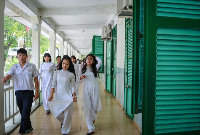 Hành lang dãy lớp học của trường mang đậm lối kiến trúc Pháp với khung cửa sổ gỗ sơn màu xanh, tường sơn trắng.