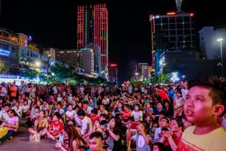 Đông đảo người dân chăm chú lắng nghe các ca khúc về tình yêu Tổ quốc thông qua hai màn hình lớn đặt trước Công viên tượng đài Hồ Chí Minh.