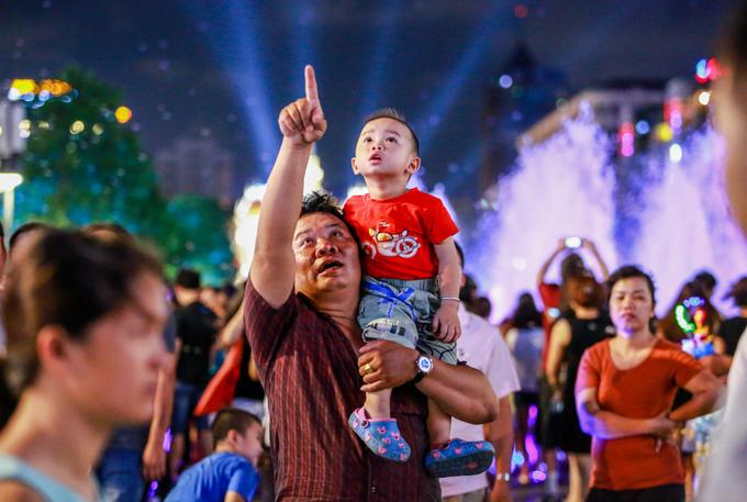 """Anh Trần Ninh (quận 6) đưa con trai 2 tuổi đi chơi trên phố. """"Cuối tuần, tôi thường cùng gia đình đi chơi. Bữa nay ngày lễ, tôi thấy không khí trên phố đi bộ đông và vui hơn nhiều với ngày thường, dù không có pháo hoa như mọi năm"""", anh Ninh nói."""