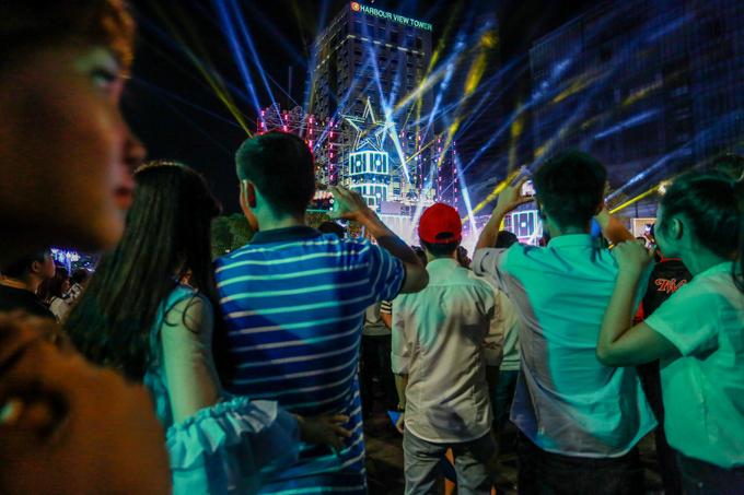Nhiều bạn trẻ dùng điện thoại ghi lại những màn trình diễn sôi động trên sân khấu chương trình Việt Nam vươn cao.