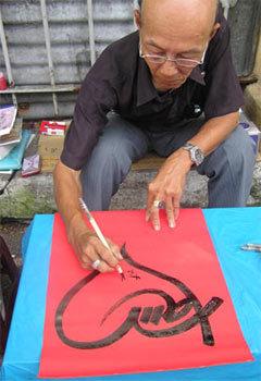 Ông Lê Việt Hà đang viết chữ Tâm. Ảnh: Dân Trí.