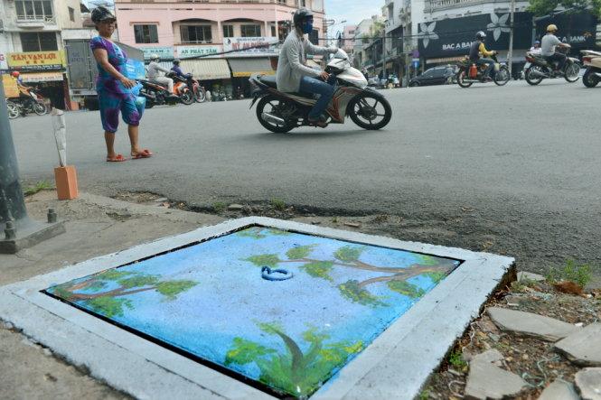 Chiếc nắp cống được sơn khiến cho phố phường sinh động hơn hẳn - Ảnh: DUYÊN PHAN