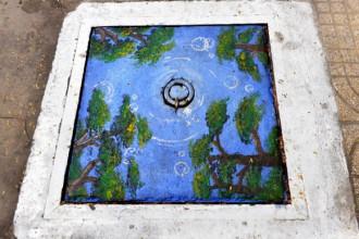 Một chiếc nắp cống được trang trí như một bức tranh phong cảnh trên đường Triệu Quang Phục (Q.5, TP.HCM) - Ảnh: DUYÊN PHAN